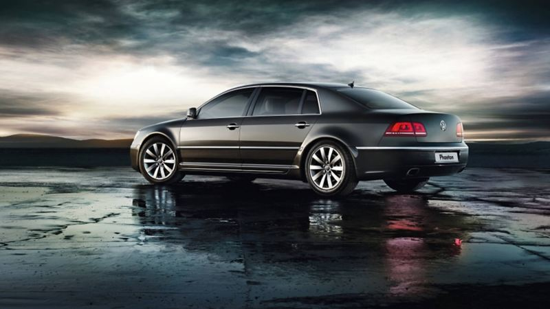 Profile shot of a grey Volkswagen Phaeton, on a wet beach, the tide out.