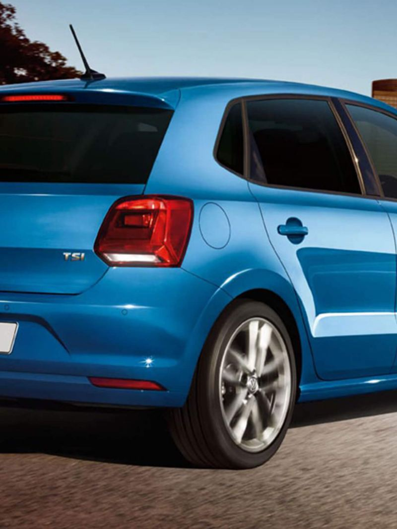 A blue Volkswagen Polo, in a city setting,