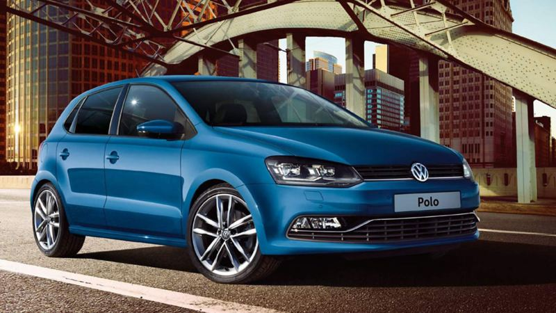 A blue Volkswagen Polo, under a steel structure, in a city setting,