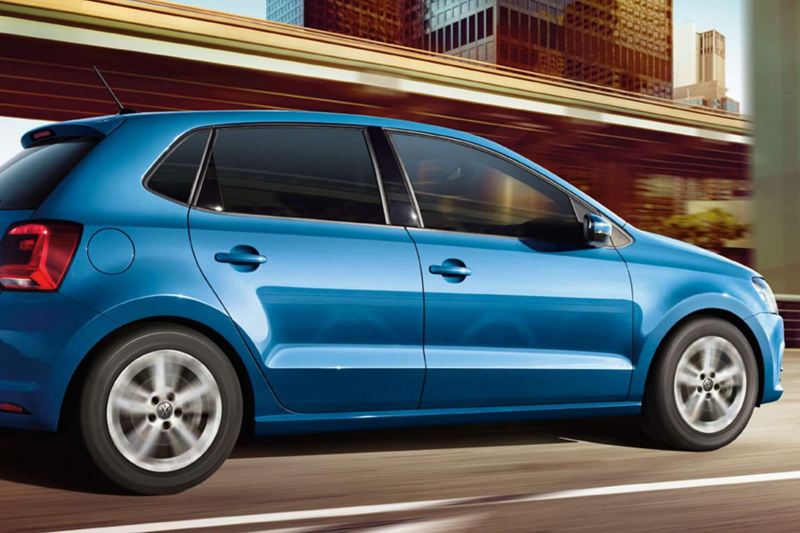 Profile shot of a blue Volkswagen Polo, driving through a city.