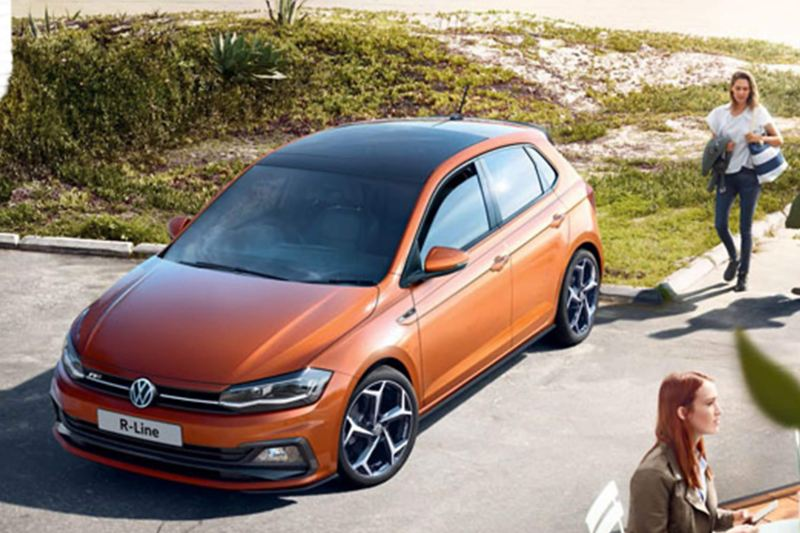 Orange Volkswagen Polo driving along a coastal road.