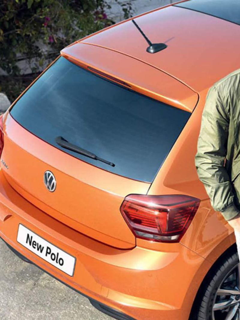 Man leaning on the side of a orange Polo.