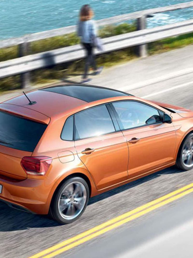 Orange Volkswagen Polo driving along a coastal road.
