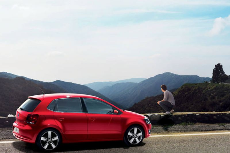 Red Volkswagen Polo, parked at the side of a mountain road.