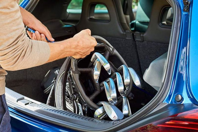man taking golf clubs out of Scirocco car