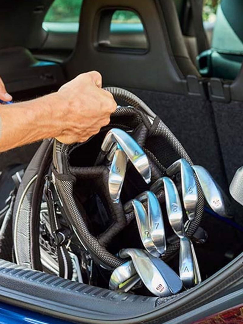 Man putting golf clubs into the boot of his Volkswagen Scirocco.