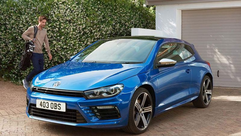 A man approaching his blue Volkswagen Scirocco, in his drive.