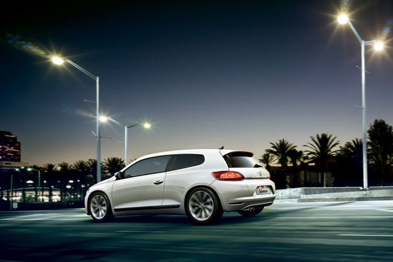 Rear profile shot of a white Volkswagen Scirocco, at dusk with palm trees in the background.