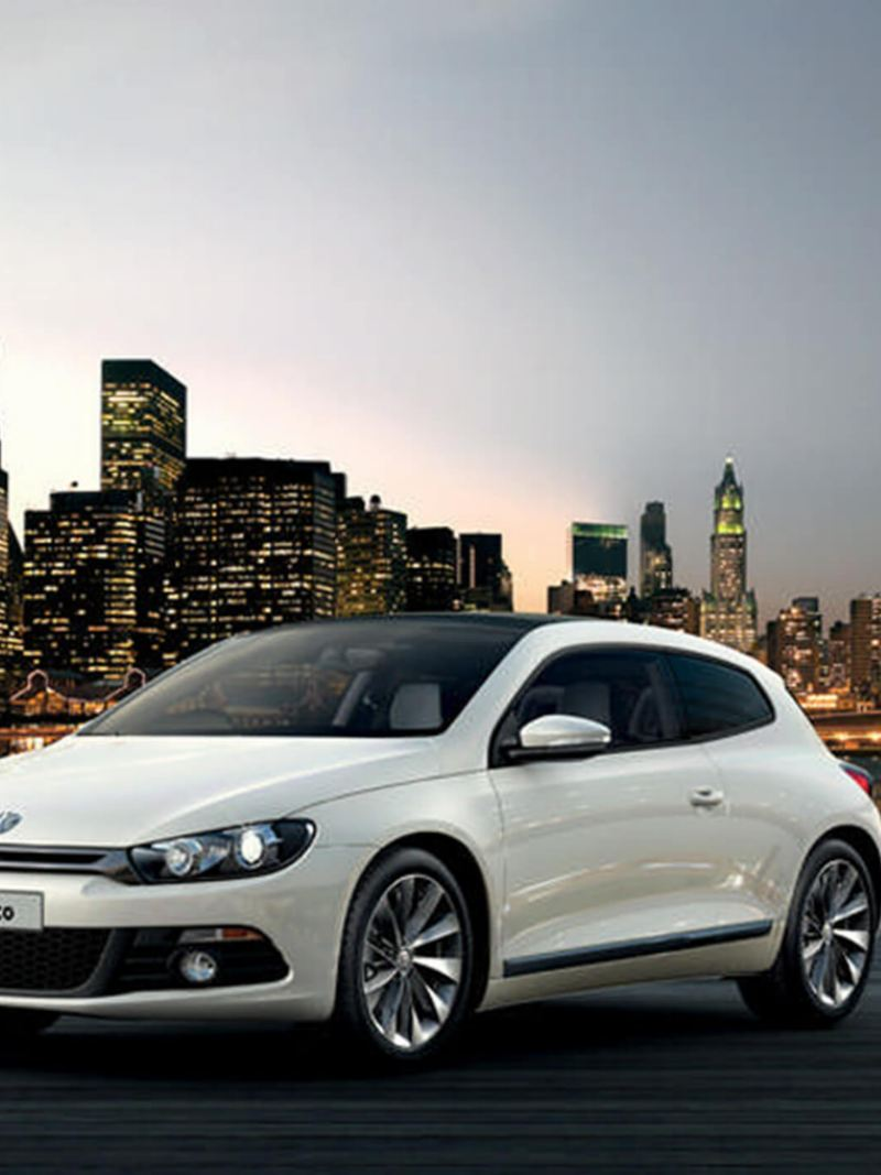 White Volkswagen Scirocco, city skyline at twilight in the background.