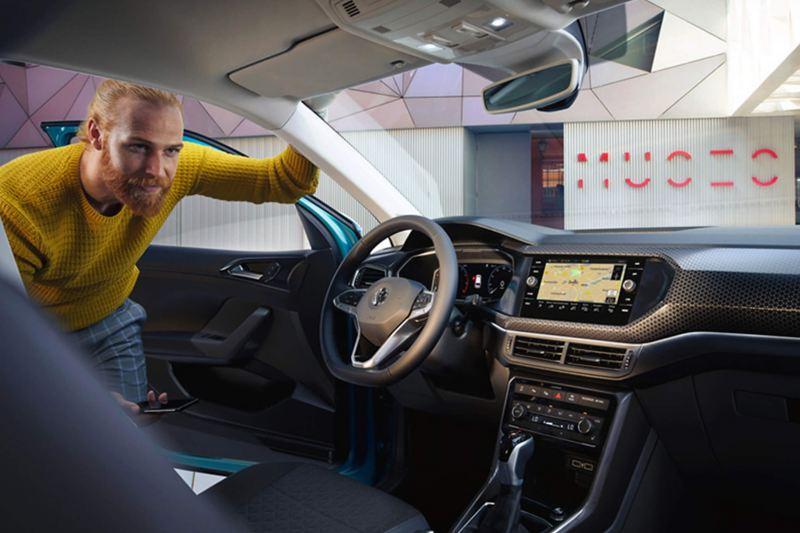 Man looking through the drivers door, at the interior of a Volkswagen T-Cross.