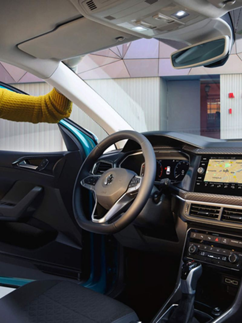 Man looking through the drivers door, at the interior of a Volkswagen T-Cross.
