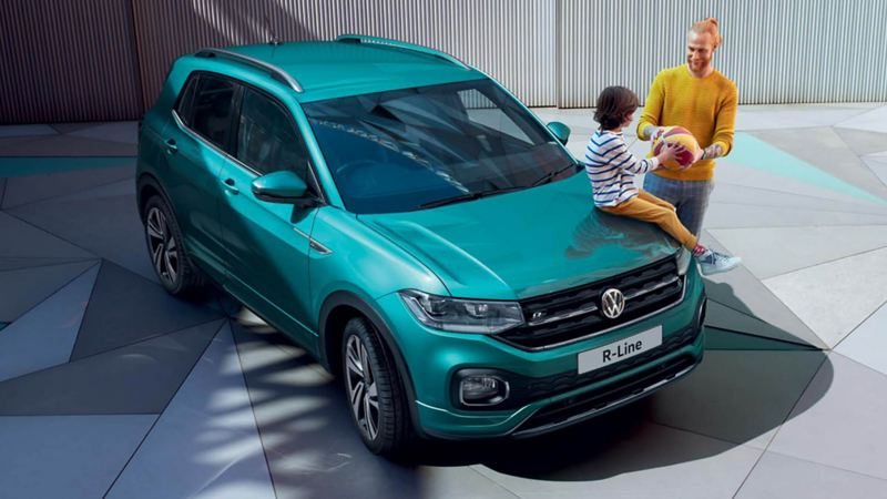 Young child sat on top of a green Volkswagen T-Cross, with her father.