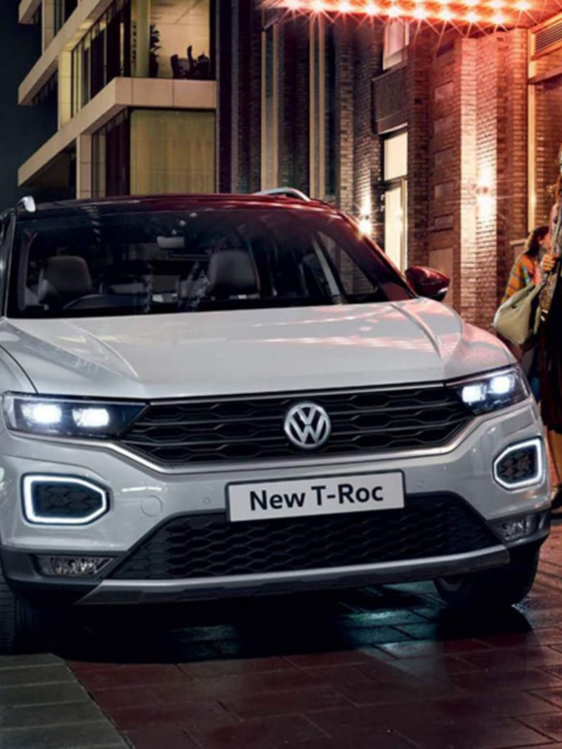A man and woman getting into a white Volkswagen T-Roc.