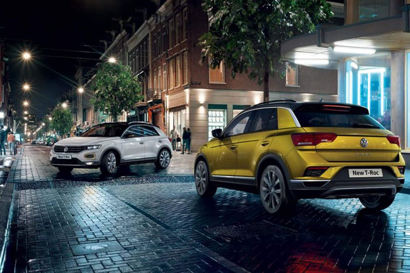 A white and a yellow Volkswagen T-Roc, on a city street at night.