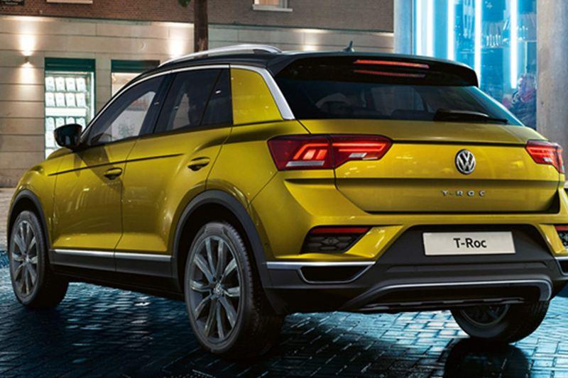 Rear shot of a yellow Volkswagen T-Roc, on a dark brick road.