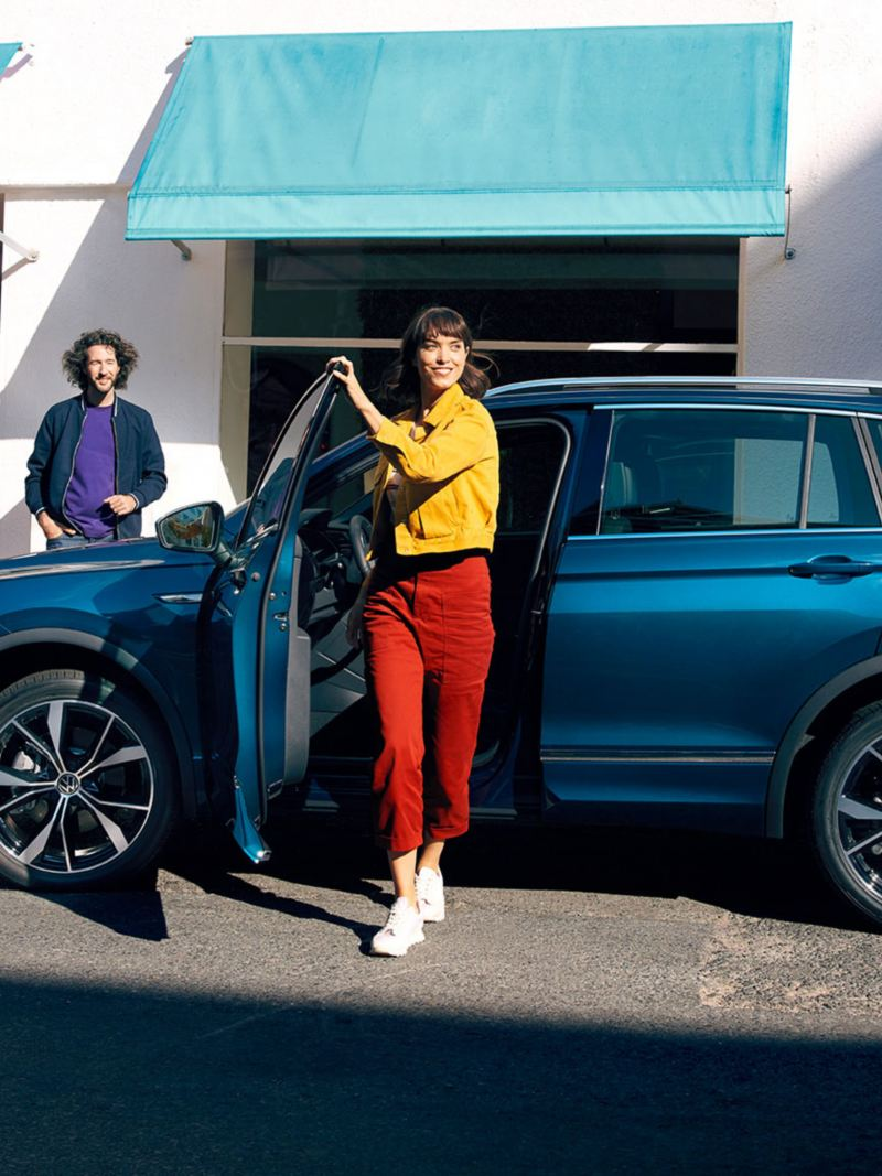 A side view of a Blue new Tiguan parked infront of a shop, with a woman in bright clothing stepping out the passenger side.