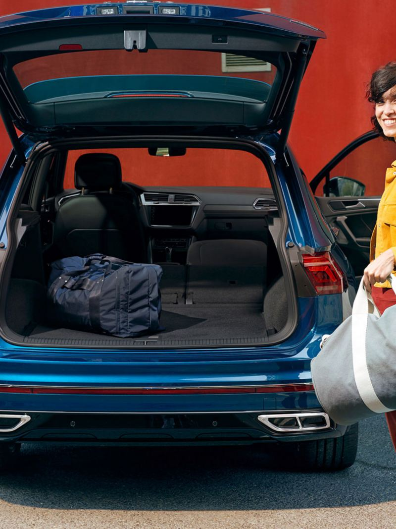 An image of a blue New Tiguans spacious boot, with a woman putting a bag into it.