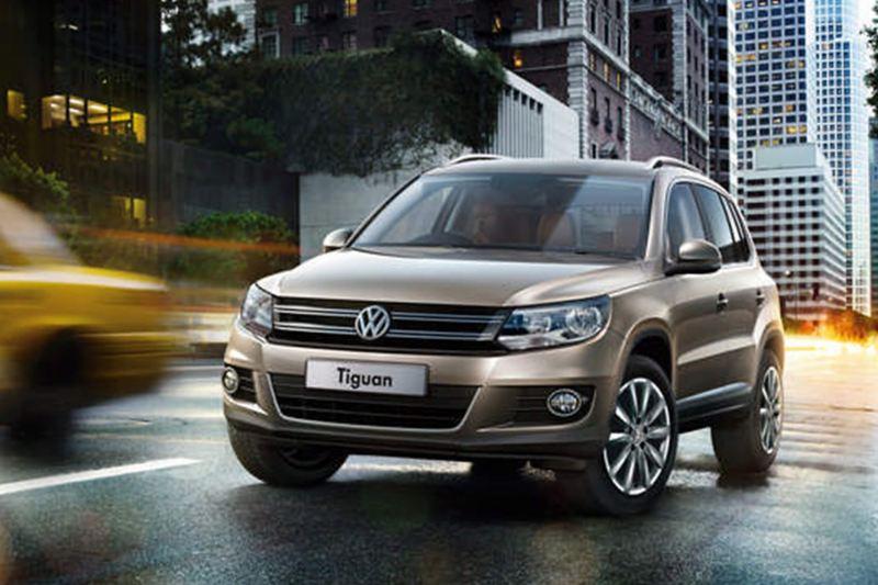 A bronze Volkswagen Tiguan, driving through a city in the evening.