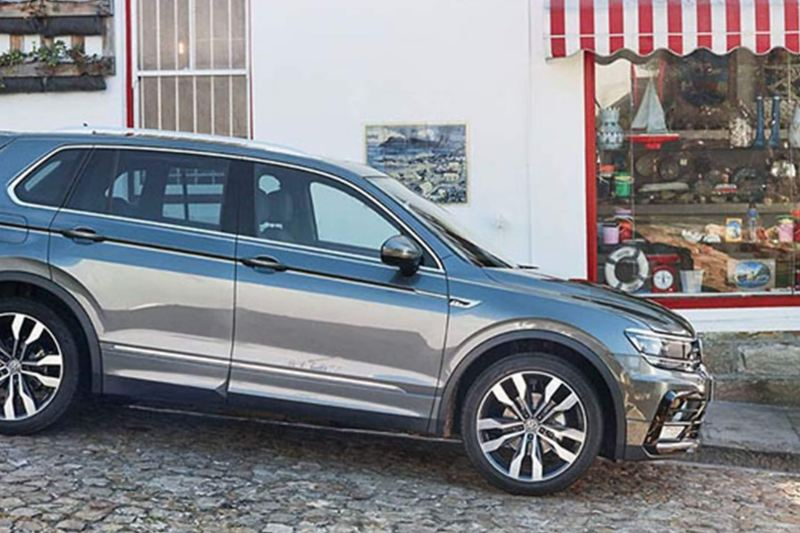 Grey Volkswagen Tiguan, on a slopping cobble street.
