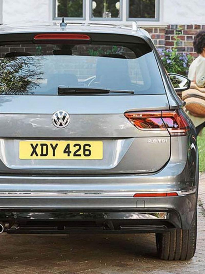 Rear shot of a grey Volkswagen Tiguan, parked as a couple walk away.