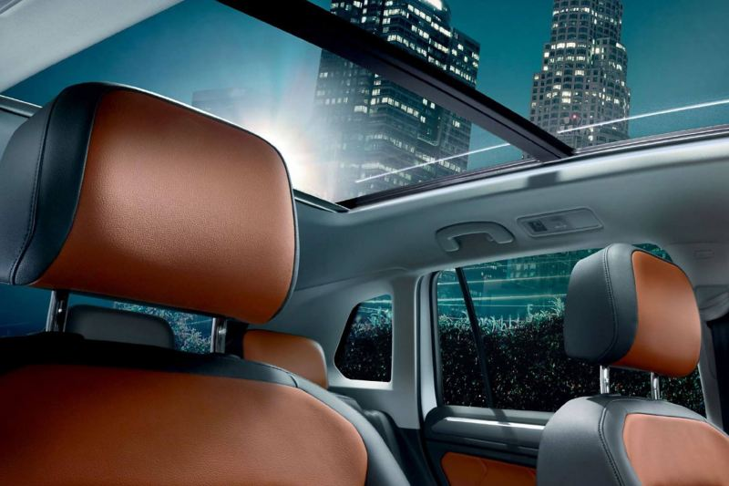 Interior shot of a Volkswagen Tiguan seats and sunroof, skyscrapers in the background.