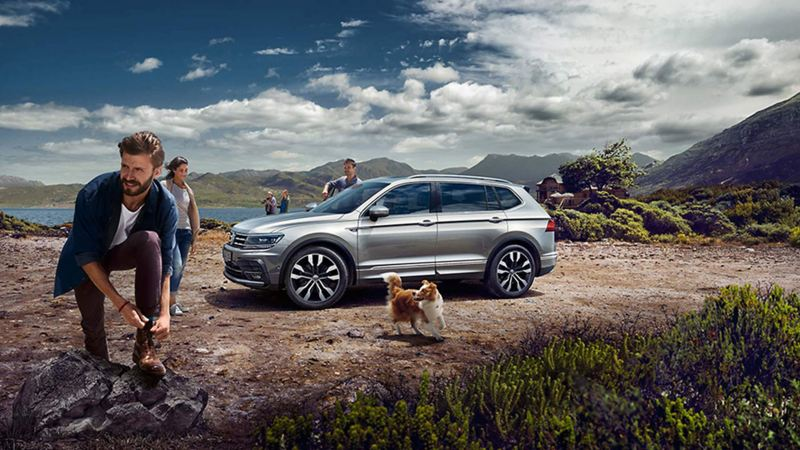 Some friends stood outside of a parked silver Tiguan Allspace