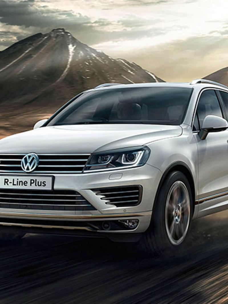 White Volkswagen Touareg R-Line Plus, driving on a mountain road.