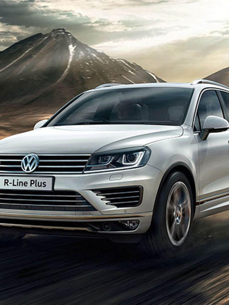 White Volkswagen Touareg R-Line Plus, driving on a mountain road.