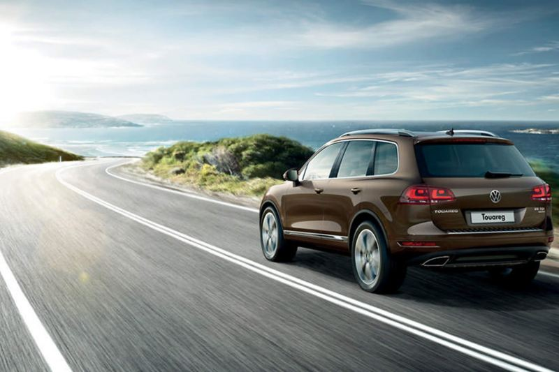 Bronze Volkswagen Touareg, rear shot, on a coastal road.