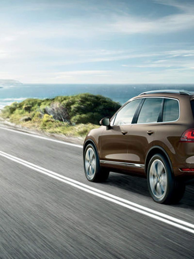 Bronze Volkswagen Touareg, rear shot, on a coastal road.