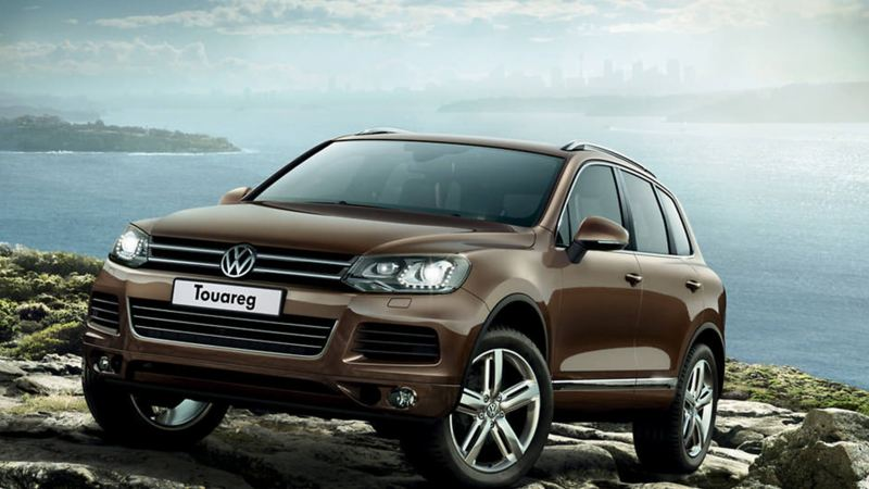 Bronze Volkswagen Touareg, ascending up a rock next to the sea.