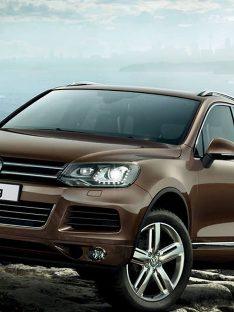 Bronze Volkswagen Touareg, ascending up a rock next to the sea.