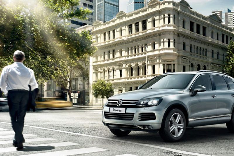 Man crossing the road, whilst a silver Volkswagen Touareg waits.