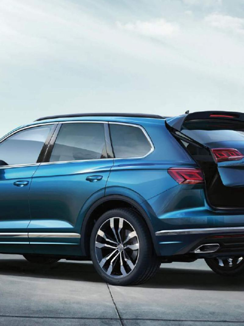 Lady with bags using the hands-free sensor to open the boot of a blue Volkswagen Touareg.