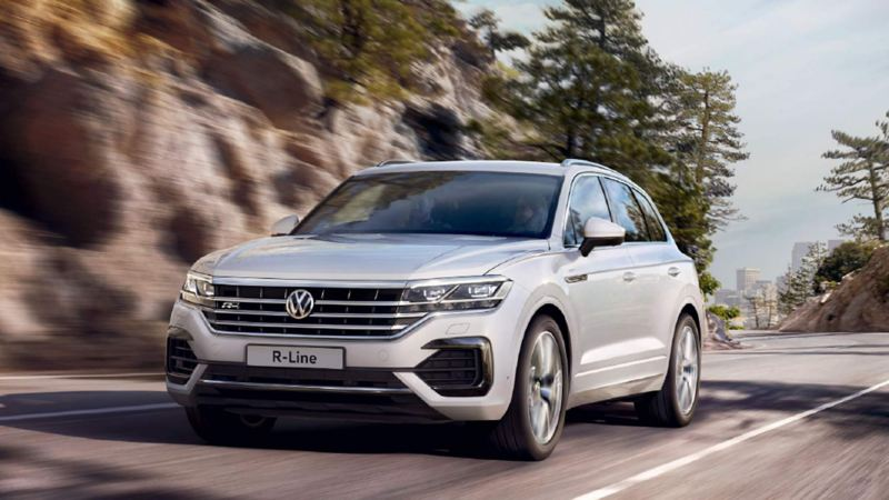 Silver Volkswagen Touareg, driving up a mountain road.