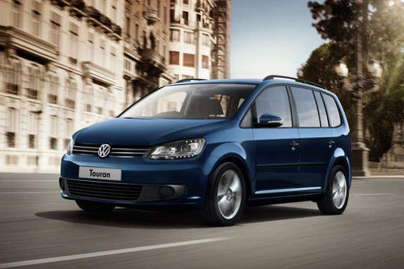 Blue Volkswagen Touran, driving through a city.