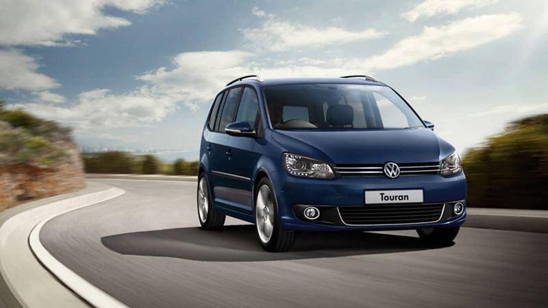 Blue Volkswagen Touran, driving on a bendy coastal road.