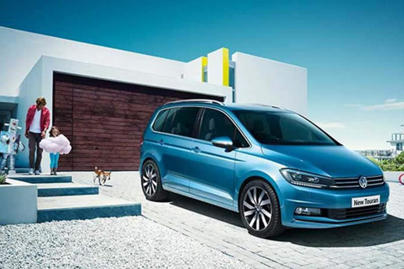 Family and dog with approaching a blue Volkswagen Touran.