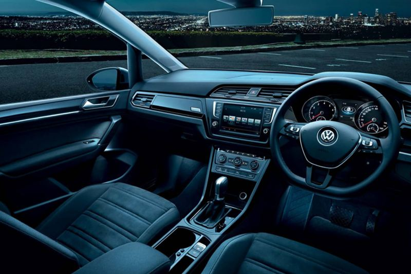 Interior shot of a Volkswagen Touran, steering wheel and dashboard, with a city skyline in the background.