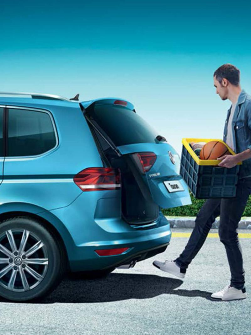 A man with a box  using the hands-free sensors to open the boot of a blue Volkswagen Touran.