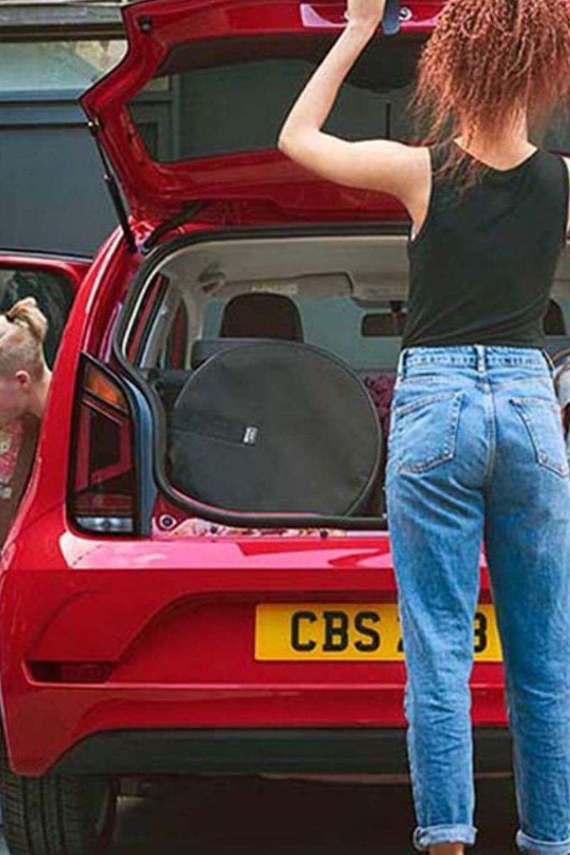 Rear shot of two ladies around a red Volkswagen up!