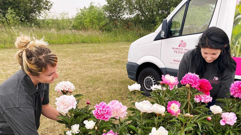 Primrose Hall with peonies next to their converted Volkswagen Crafter