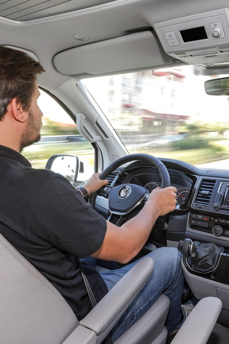 man driving VW California in sunny city street