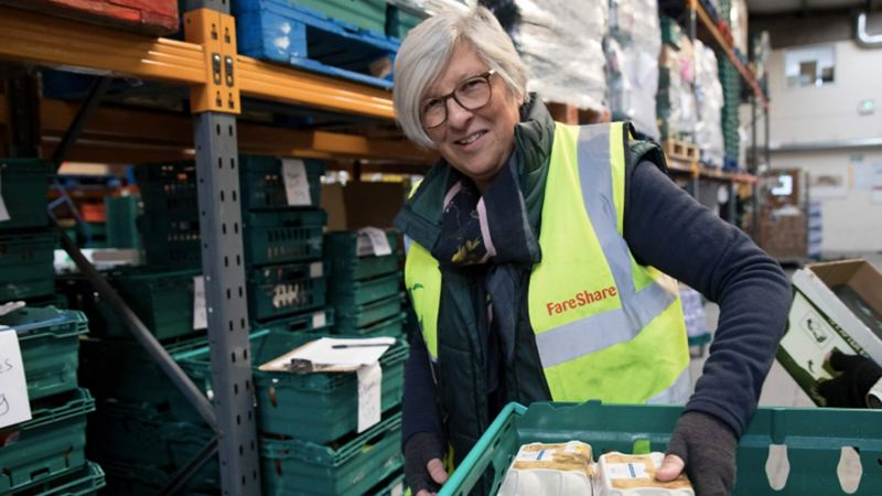 An employee of FareShare with a crate of food