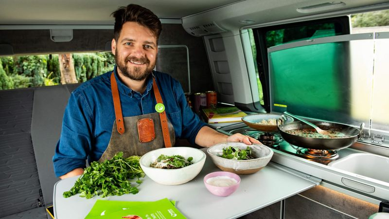 Chef Tom sitting inside a California camper van with some ingredients
