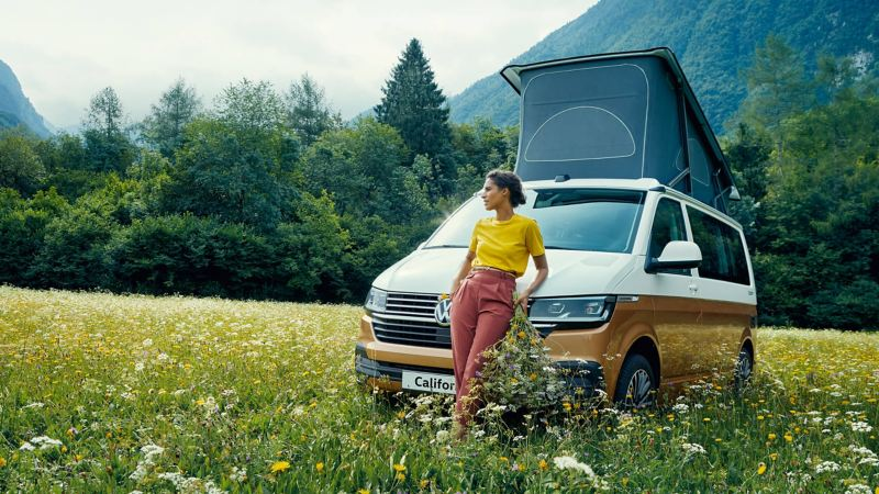 Women in field resting against a California camper van