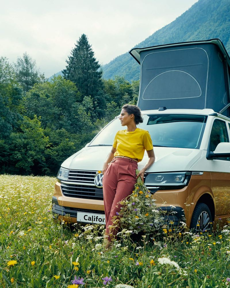 Woman leaning against California camper van in a field