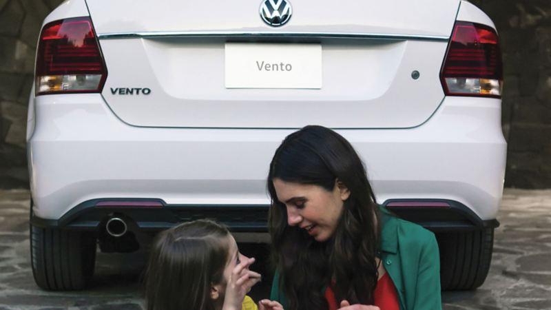 Madre e hija sentadas frente a vista trasera de Vento 2020 de Volkswagen México
