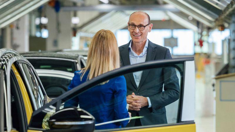 Ralf Brandstätter in conversation next to an VW ID.4