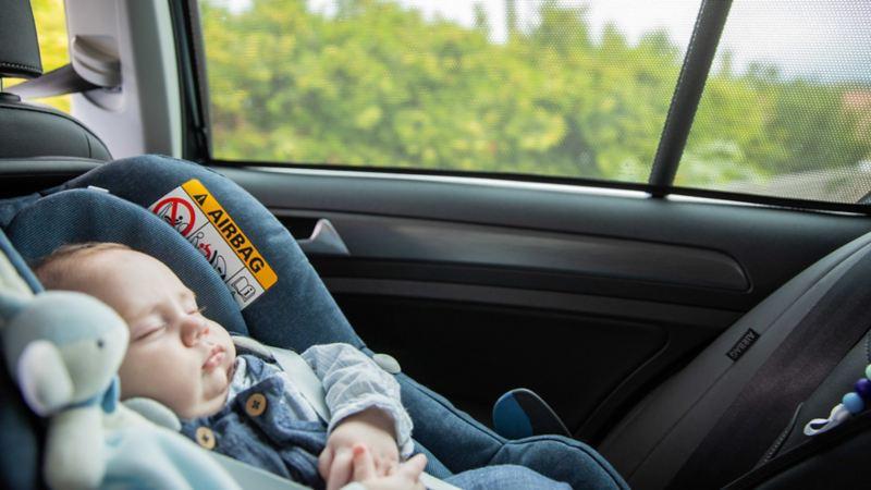 Et barn sover i en bilstol i baksetet på en Volkswagen e-Golf elbil med solskjerm